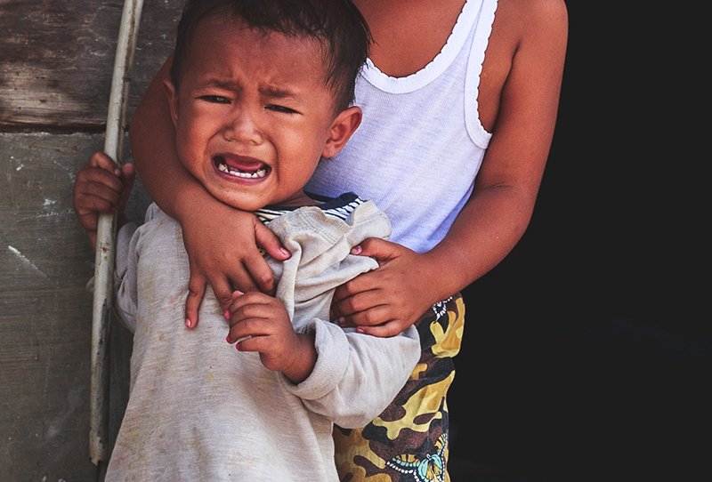 a crying toddler is held by a sybling